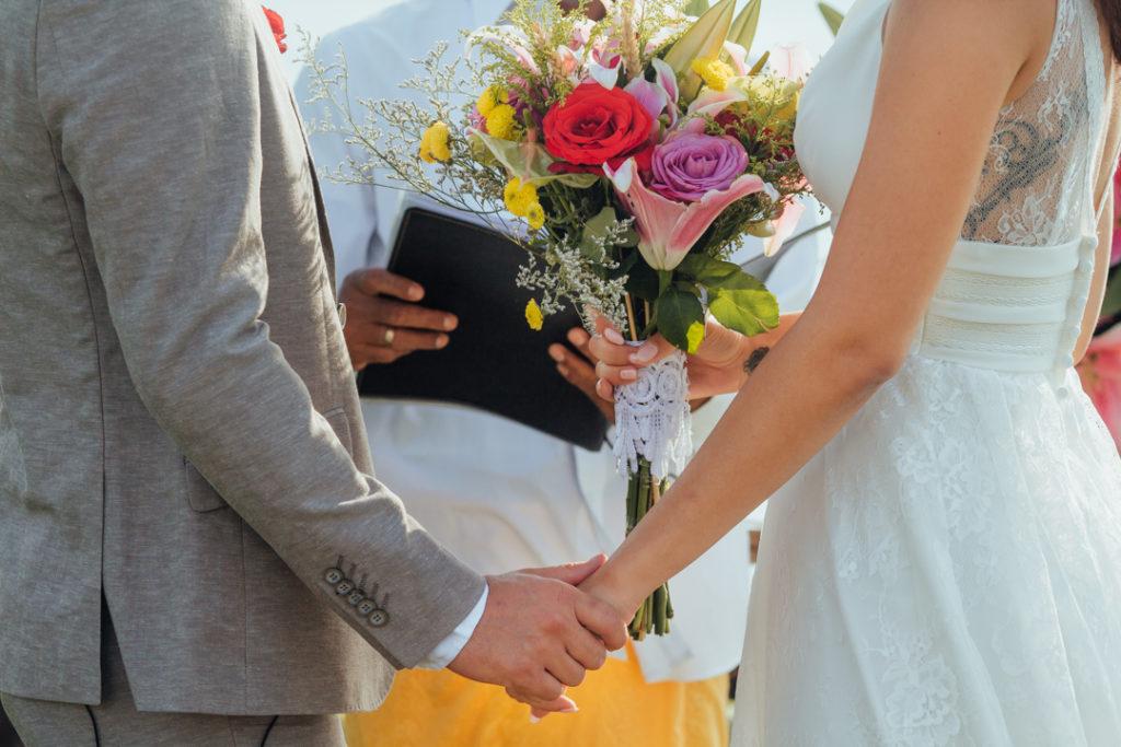 Les maries se tiennent la main avec le bouquet
