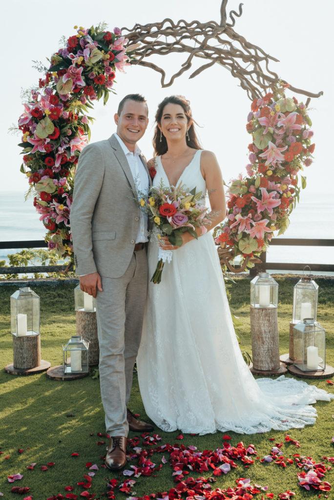Les maries devant l'arche de fleurs